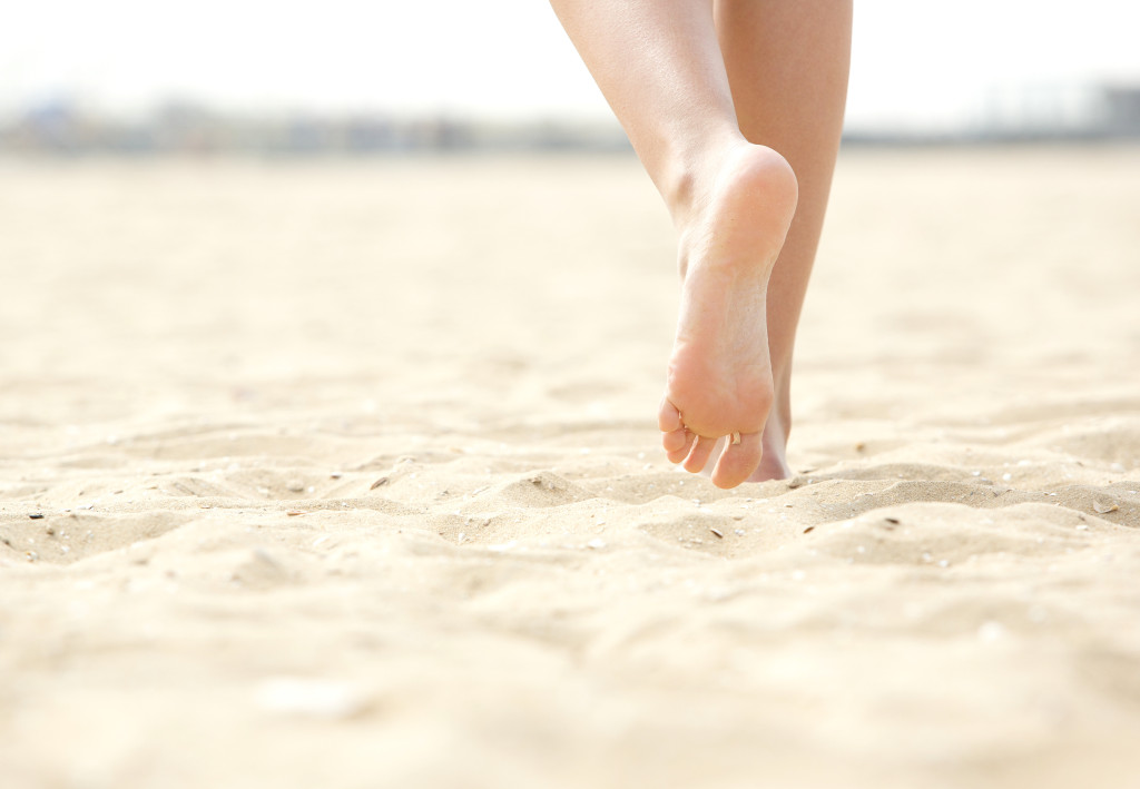 Close up low angle woman barefoot walking on beach